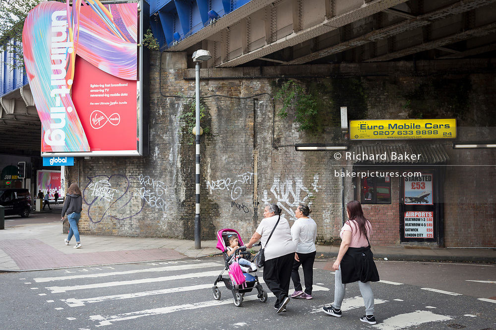 A new ad for Virgin Media fixed to an old Victorian wall beneath Waterloo station in SE1, on 19th August 2019, in London, England.