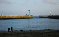 © Licensed to London News Pictures. <br /> 15/03/2015. <br /> <br /> Whitby, United Kingdom<br /> <br /> A couple walk their dogs on the beach at first light in Whitby in North Yorkshire.<br /> <br /> Photo credit : Ian Forsyth/LNP