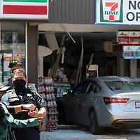 A woman who crashed her car through the front wall of the 7-11 convenience store at the corner of Ocean Street and Broadway in Santa Cruz, California explains to a police officer how she inadvertently drove into the store on Monday July 27, 2020. One worker in the store was treated for minor injuries at the scene and the driver walked away unhurt.