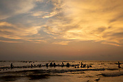 Dramatic wispy clouds in the sky above groups of people swimming in the Bay of Bengal sea during sunset on Laboni Beach, Cox Bazar, Chittagong Division, Bangladesh, Asia.