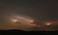Ellenville, New York - Lightning from distant thunderstorms lights up clouds in the night sky above the Catskill mountains on July 17, 2010.
