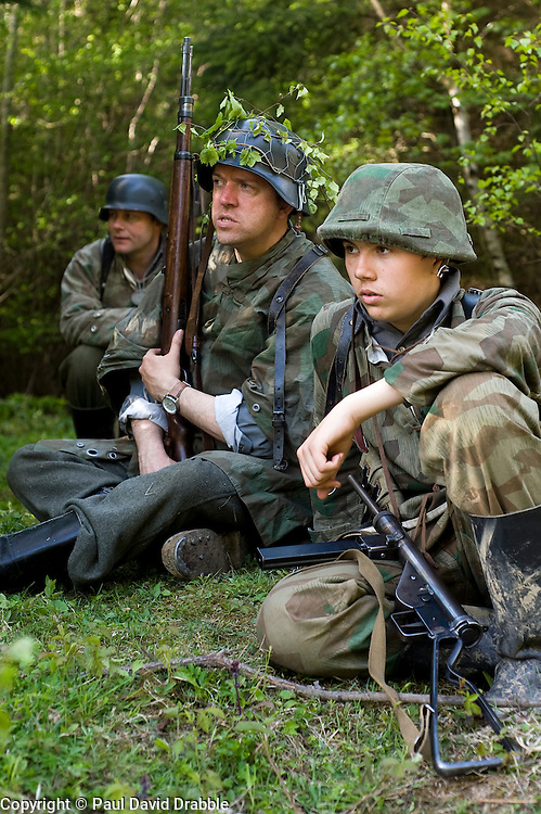 Reenactors from Northern World War Two Association, dressed as Panzer Grenadiers from the Elite Grossdeutschland Division, waiting for the return of reconnaissance party during a private 24hr excerise, held at Sutton Grange, near Ripon in Yorkshire. All are wearing the iconic coal scuttle helmets (stahlhelme) splinter pattern camouflage and Jackboots One reenactor is holding the K98 Rifle and in the foreground is a German MP3008 sub machine gun which was based on the British Sten gun.<br />  15 May 2010 15 May 2010 .Images © Paul David Drabble.