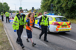 © Licensed to London News Pictures. 13/09/2021. Hertfordshire, UK. A person is arrested as protesters from climate campaign 'Insulate Britain', an offshoot of Extinction Rebellion (XR), block the A41 roundabout at Junction 20 of the M25 London Orbital Motorway. Photo credit: Peter Manning/LNP
