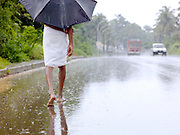 Walking barefoot along a road during the monsoon rains, Cochin, Kerala, India