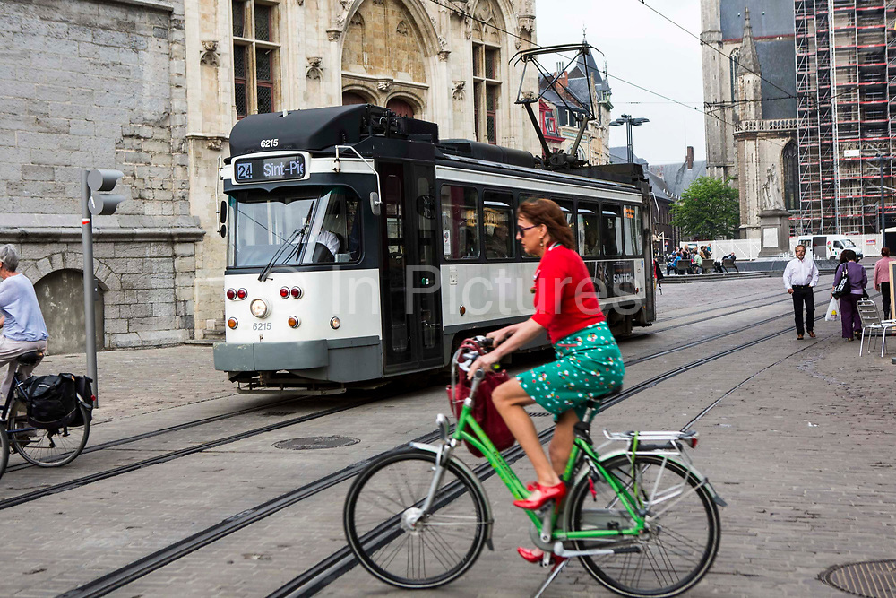 A female Belgian cyclists rides on her bicycle across tram lines of the Ghent tramway network in Gent, Belgium. An old tram travels past in the background.