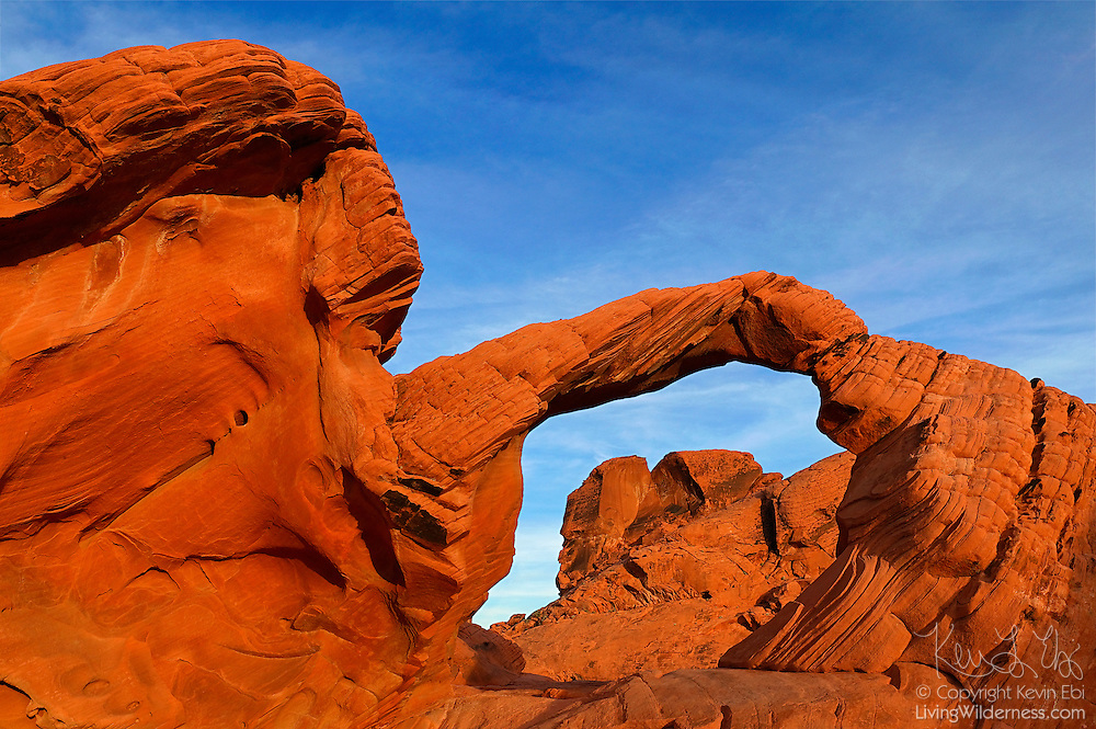 Arch Rock, one of the most famous arches in the Valley of Fire State Park, Nevada, frames another towering sandstone formation.