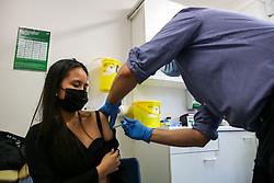 © Licensed to London News Pictures. 12/09/2021. London, UK. Nurullah Yumsak, a NHS vaccinator, administers second dose of the Moderna Covid-19 vaccine to 19 year old Van Camle at a vaccination centre in north London. Health Secretary, Sajid Javid has announced that the government has dropped plans for domestic vaccine passports for use in large venues. It has also been reported that PCR tests are to be axed for double-jabbed holidaymakers on their return to the UK. Photo credit: Dinendra Haria/LNP