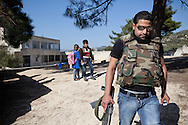 A soldier from the Free Syrian Army walks from the school in the village of Adthar, in opposition control. Adthar, Idlib, Syria. 19/11/2012