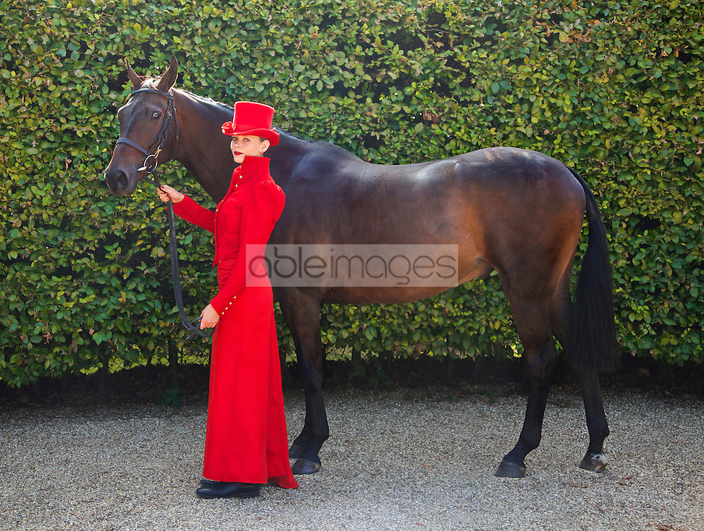 Woman in Red Equestrian Outfit Standing in front of Garden Hedge with Horse