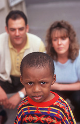 Portrait of young boy with mother and father in background,