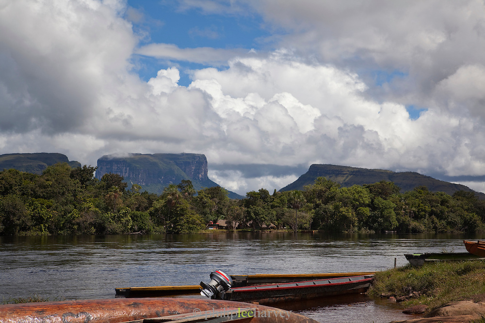 Dugout canoes moored on the Canaima River. Tepuis, large flat topped mountains, stand all along the winding river, in Canaima National Park, Venezuela