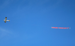 A plane flies over the pitch during the match displaying a banner which says Kroenke - You're next