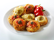 Mini potato rosti topped with tomato salsa and capers and melted cheese and olives