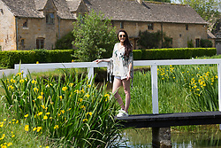 © Licensed to London News Pictures. 25/05/2017. The Slaughters, Cotswolds, UK. Pictured, HEIDI PERKINS from Sydney, Australia on holiday visiting her father, a London taxi cab driver. HEIDI is pictured on the walking bridge in the centre of the Slaughters, a well known tourist spot in the Cotswolds. Photo credit: Dave Warren/LNP