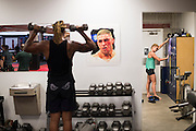UFC bantamweight Holly Holm of Albuquerque gets her gear ready for sparing while another fighter lifts weights at Jackson Wink MMA in Albuquerque, New Mexico on June 9, 2016.