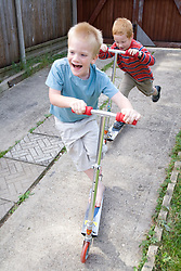Two brothers playing in the garden on scooters,