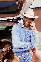 cowboy talking on a cellphone by a truck