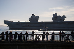 © Licensed to London News Pictures. 30/10/2017. Portsmouth, UK.  A woman waves as people gather to watch the Royal Navy's flagship, HMS Queen Elizabeth, as she departs Her Majesty's Naval Base (HMNB) Portsmouth for the first time since her arrival on 16/08/2017.  The new aircraft carrier is heading back to sea for the second stages of her sea trials.<br /> <br /> Flight trials involving the new F-35B Joint Strike Fighter are expected to take place off the coast of the U.S. next year, and she is due to come into service in the early 2020s.  Photo credit: Rob Arnold/LNP