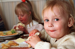 Portrait of young girl with Downs syndrome eating meal at table with younger sister,