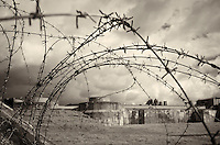 Looking Through the Barbed-Wire Fence into the WWII Prison Camp at Fort Breendonk Near Antwerp in Belgium. Image taken with a Leica X2 camera (ISO 100, 24 mm, f/6.3, 1/800 sec). Raw image processed with Capture One Pro 7 (including conversion to B&W).