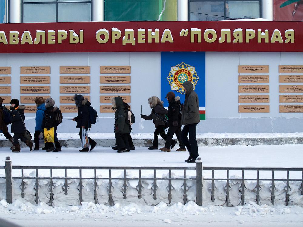 Schulklasse in der Innenstadt von Jakutsk. Jakutsk wurde 1632 gegruendet und feierte 2007 sein 375 jaehriges Bestehen. Jakutsk ist im Winter eine der kaeltesten Grossstaedte weltweit mit durchschnittlichen Winter Temperaturen von -40.9 Grad Celsius. Die Stadt ist nicht weit entfernt von Oimjakon, dem Kaeltepol der bewohnten Gebiete der Erde.<br /> <br /> School class in the city center of Yakutsk. Yakutsk was founded in 1632 and celebrated 2007 the 375th anniversary - billboard announcing the celebration. Yakutsk is a city in the Russian Far East, located about 4 degrees (450 km) below the Arctic Circle. It is the capital of the Sakha (Yakutia) Republic (formerly the Yakut Autonomous Soviet Socialist Republic), Russia and a major port on the Lena River. Yakutsk is one of the coldest cities on earth, with winter temperatures averaging -40.9 degrees Celsius.