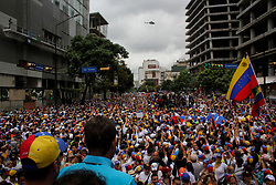 Deputy to the National Assembly Juan Requesens points to helicopter as he speaks in front of hundreds of opponents in Altamira this May 1, 2017.