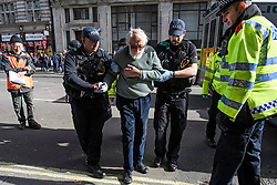 © Licensed to London News Pictures. 10/10/2019. London, UK. An elderly Extinction Rebellion activists being arrested for refusing to move from the roads around Trafalgar Square in Westminster, central London where campaigners have been demonstrating for a fourth day running. The climate change group have blockaded the Westminster area, demanding that the government takes immediate and decisive action on climate change. Photo credit: Ben Cawthra/LNP