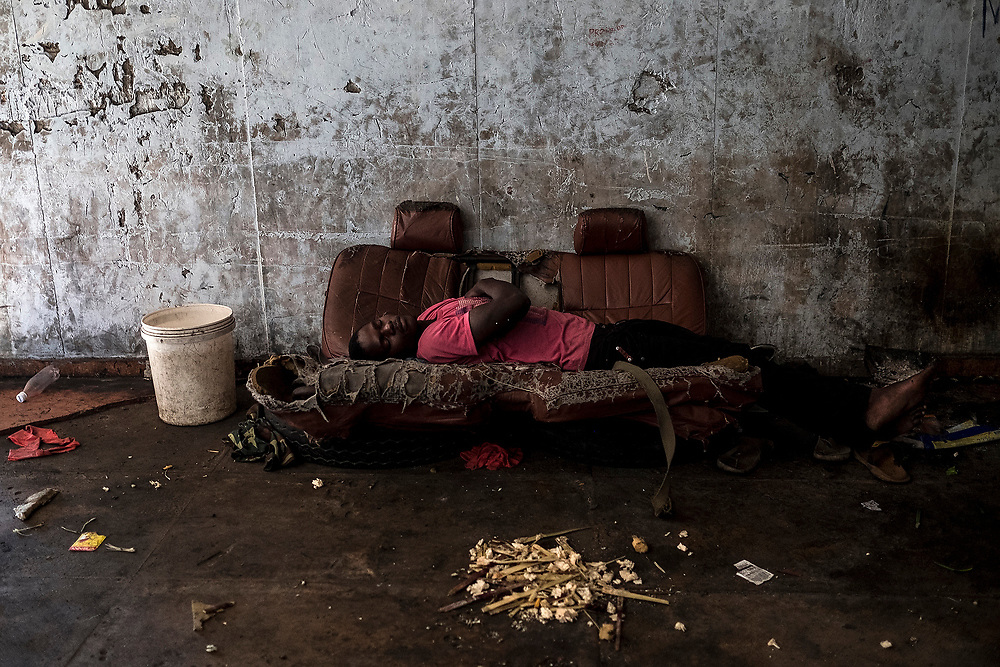 """BEIRA, MOZAMBIQUE - JUNE 26, 2016: <br /> A boy sleeping on the couch in his """"house"""" at the hotel entrance. Many residents do not have rooms. The building has 3 floors with 122 rooms."""