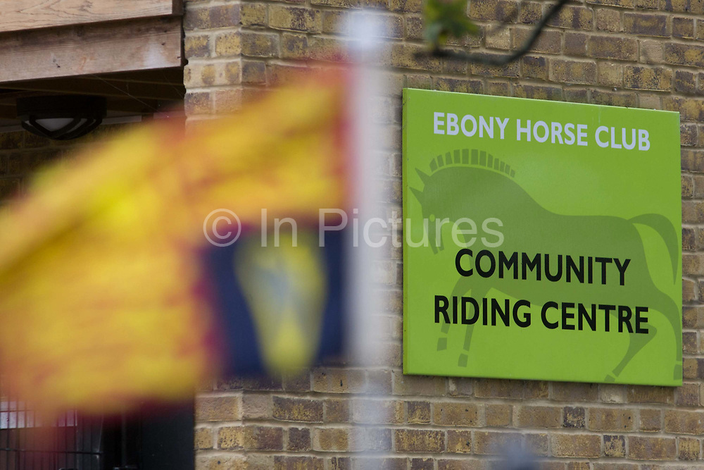 The royal standard as Queen Elizabeth makes a brief visit to the Ebony Horse Club at Loughborough Junction, Brixton, London. Accompanied by the Duchess of Cornwall, Her Majesty watched an equestrian demonstration in one of the most disadvantaged inner city neighbourhoods in the country where there is a historic legacy of under-achievement in schools, high rates of teenage pregnancy and negative stereotypes of young people, gang violence and drug related crime.