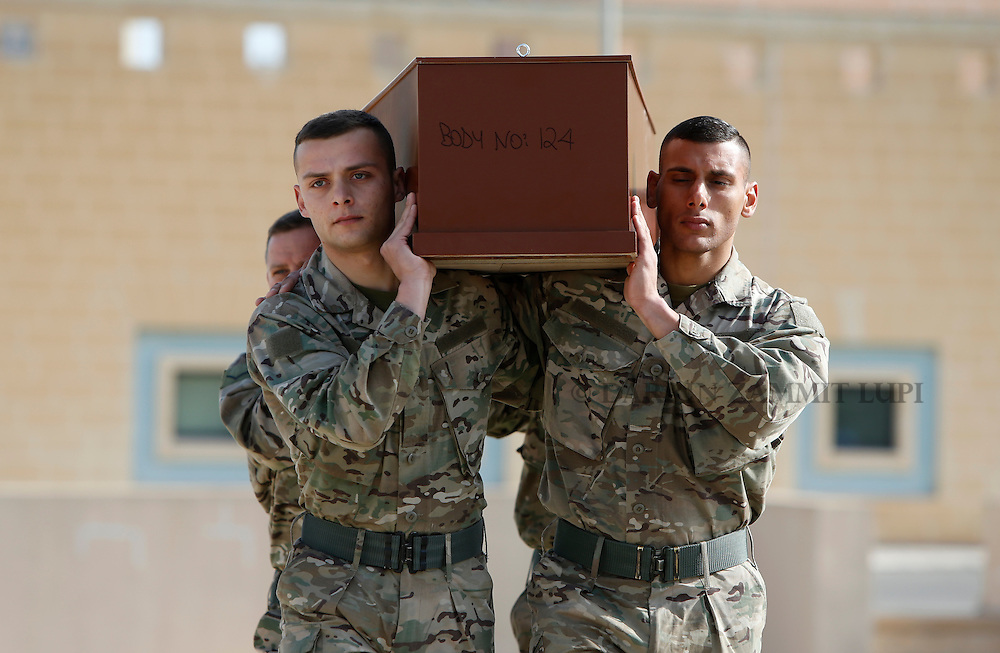 Armed Forces of Malta soldiers carry a coffin with the body of a migrant to an inter-faith burial service at Mater Dei Hospital in Tal-Qroqq, outside Valletta, April 23, 2015. European Union leaders who decided last year to halt the rescue of migrants trying to cross the Mediterranean will reverse their decision on Thursday at a summit hastily convened after nearly 2,000 people died at sea.  Public outrage over the deaths peaked this week after up to 900 migrants died last Sunday when their boat sank on its way to Europe from Libya.<br /> REUTERS/Darrin Zammit Lupi MALTA OUT. NO COMMERCIAL OR EDITORIAL SALES IN MALTA
