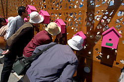 Visitors looking at photographs inside birdboxes at British Pavilion at World Expo 2005 in Aichi Nagoya Japan