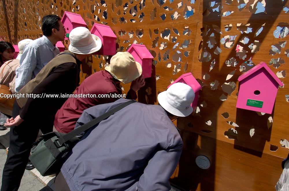 Visitors looking at photographs inside birdboxes at British Pavilion at World Expo 2005 in Aichi Nagoya Japan