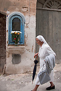A nun walks past a shrine dedicated to the Madonna in the streets of Favignana town, Aegadian Islands (Isole Egadi), western Sicily, Italy