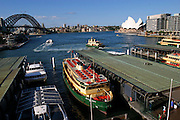 Boats dock at Sydney Harbour, with the Harbour Bridge and  Opera House in the background in Sydney,  New South Whales, Australia.
