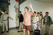 """23 JANUARY 2013 - BANGKOK, THAILAND:   SOMYOT PRUESAKASEMUK waves the """"V for Victory"""" as he walks into Bangkok Criminal Court followed by court security Wednesday. Somyot was sentenced to 11 years imprisonment Wednesday for violations of Thailand's """"Lese Majeste"""" laws. He was arrested on April 30, 2011, and charged under article 112 of Thailand's penal code, which states that """"whoever defames, insults or threatens the King, the Queen, the Heir-apparent or the Regent, shall be punished with imprisonment of three to fifteen years"""" after the magazine he edited, """"Red Power"""" (later changed to """"The Voice of Thaksin"""") published two articles by Jit Pollachan, the pseudonym of Jakrapob Penkair, the exiled former spokesman of exiled fugitive former Prime Minister Thaksin Shinawatra. Jakrapob, now living in Cambodia, has never been charged with any crime for what he wrote.     PHOTO BY JACK KURTZ"""
