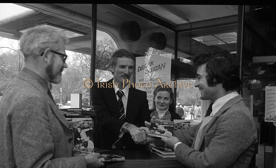 Derek Dougan's name goes in the book...1980-04-16.16th April 1980.16-04-1980.04-16-80..Photographed at Hodges Figgis, Stephen's Court, St Stephen's Green, Dublin:..Fromer Northern Irish soccer international and English League player Derek Dougan signing a copy of his book 'Doog' for customer Peter Moynihan, Sandyford, Co Dublin (right of picture)...Also in picture..Robert Twigg, manager of Hodges Figgis and cashier Norma Doyn (Tallaght, Dublin)....