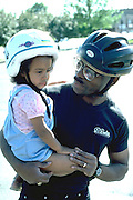 Father holding daughter wearing bicycle helmets age 26 and 3.  Minneapolis Minnesota USA