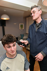 Life in Lockdown in the UK March & April 2020<br /> A father and son cut each others hair, under lockdown using some clippers. Model released.