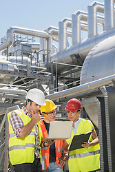 Engineer with his colleagues in meeting with laptop at geothermal power station, Bavaria, Germany