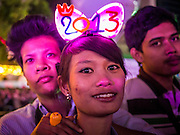 """31 DECEMBER 2012 - BANGKOK, THAILAND:  Thai teenagers at the New Year's Eve Party in Ratchaprasong Intersection in Bangkok. The traditional Thai New Year is based on the lunar calender and is celebrated in April, but the Gregorian New Year is celebrated throughout the Kingdom, especially in larger cities and tourist centers, like Bangkok, Chiang Mai and Phuket. The Bangkok Countdown 2013 event was called """"Happiness is all Around @ Ratchaprasong."""" All of the streets leading to Ratchaprasong Intersection were closed and the malls in the area stayed open throughout the evening.   PHOTO BY JACK KURTZ"""
