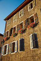 A historic, Neo-Classic Facade building which includes window boxes, flowers, shutters, and windows, Old Town Annecy, France.