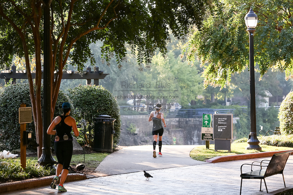 Runners along the Swamp Rabbit Trail and bike path in Falls Park on the Reedy River in downtown Greenville, South Carolina.