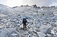 A woman standing using her hydration pack in a boulder / talus field in the Upper Enchantment Lakes Wilderness area, Cascade mountains, Washington, USA.