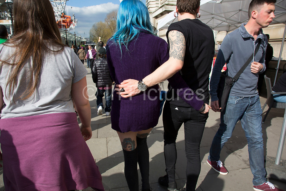 Impressive tattoos on a couple as they walk with their arms around each other on the walkway. The South Bank is a significant arts and entertainment district, and home to an endless list of activities for Londoners, visitors and tourists alike.