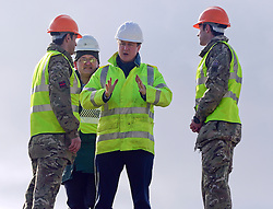 © Licensed to London News Pictures. 10/02/2014. Portland, UK Prime Minister David Cameron visits Chesil Beach Beach in Portland to see the work being done by the Environment Agency and 39 Royal Engineer Regt. Early this week adverse weather and high tide breach the high beach flood defences, washing away a large portion of the stones. Over the weekend the Royal Engineers deployed bulldozers and diggers to help the Environment Agency rebuild the defences. The Prime Minister met both Agency workers and soldiers that had been working on the rebuild.. Photo credit : Russ Nolan/LNP