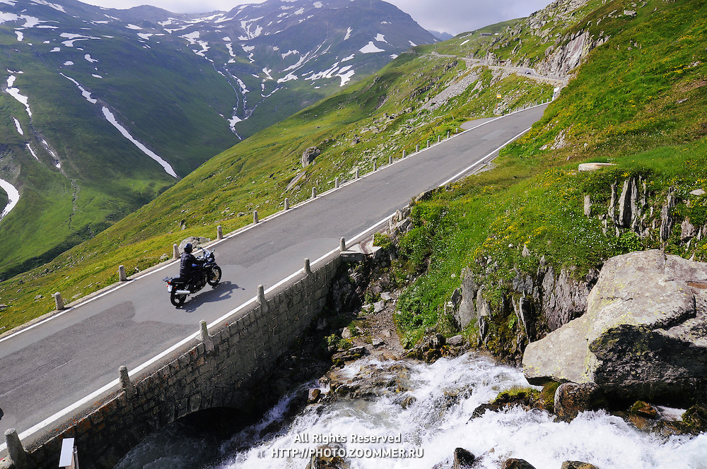 Perspective of Alpine road with biker