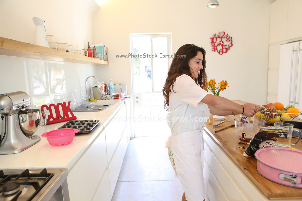 Teen in white apron bakes a cake in the kitchen