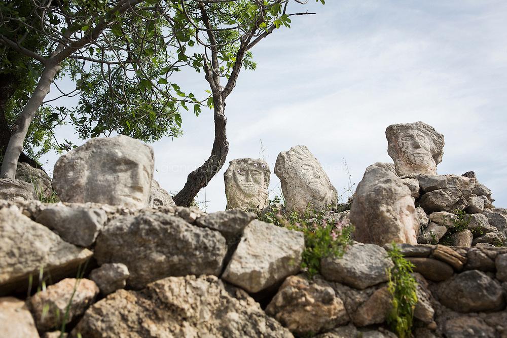 """SCIACCA (AG), ITALIA - 22 APRILE 2015: Le sculture d Filippo Bentivegna, teste umane scolpite nella roccia, nel Castello Incantato a Sciacca il 22 aprile 2015. Filippo Bentivegna (1888-1967) è stato uno scultore italiano, protagonista della corrente dell'Art Brut. Senza nessuna formazione artistica, realizzò migliaia di sculture materializzando il """"Castello incantato"""" nel suo podere di Sciacca oggi divenuto un museo all'aperto."""