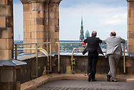 Riga, Latvia - August 26, 2015: Two men talk and enjoy the view from the roof of the Academy of Science, a Soviet-era highrise, in Riga, Latvia