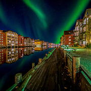 """Amazing aurora over Trondheim Brygga and Nidelva river. Here you can see one over the beautiful wooden houses of Trondheim. please note that  some of the green lights come from sidewalk lamps on the ground :).This picture has been  Please feel free to find me by: <a href=""""http://www.aziznasutiphotography.com/"""">